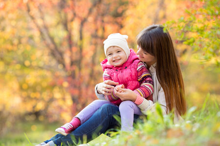 beautiful young mother and her daughter have fun sitting at autumn grass background photo