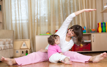 mother and kid doing gymnastic at home photo