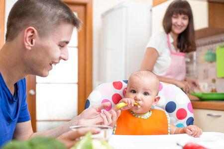 father feeding his baby and mother cooking at kitchen photo