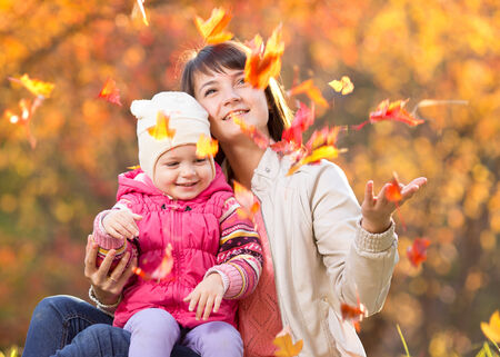 Kid and beautiful mother play and throw leaves outdoor in autumn park photo