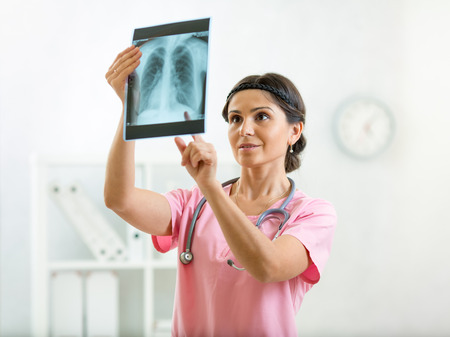 roentgenogram: doctor reviewing x-ray photo in office Stock Photo