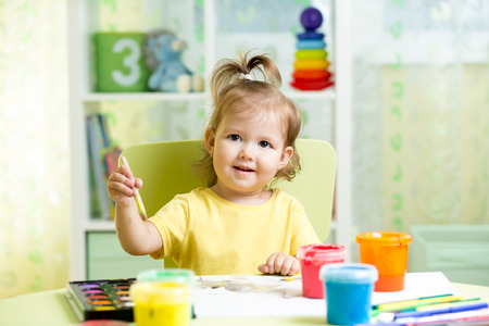 children painting: kid girl painting at table in children room