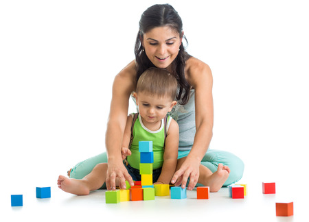 child boy and mother playing together with block toys photo
