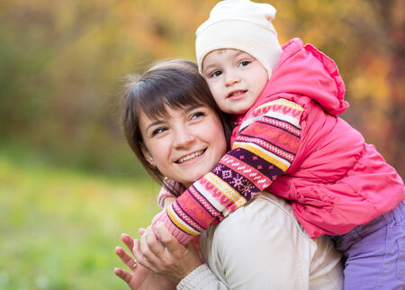 kids hugging: happy mother with kid girl outdoor in autumn park Stock Photo