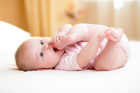 pie bebe: niña acostada y tirando de sus piernas a la boca Foto de archivo