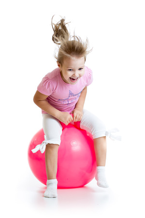 exhilarated: happy child jumping on bouncing ball. Isolated on white.