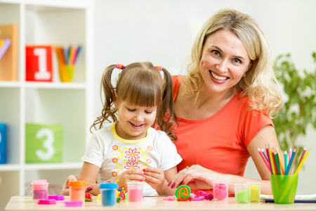 2 people at home: mom and daughter play colorful clay toy