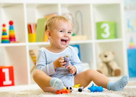 kid playing with toy animals indoors photo