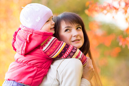 beautiful mother with kid girl outdoors in fall photo