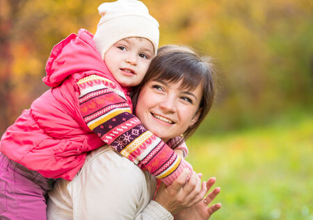 happy mother with kid girl outdoor in autumn park photo
