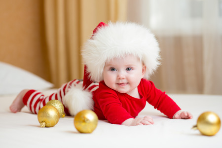 funny Santa baby girl lying on white bed photo