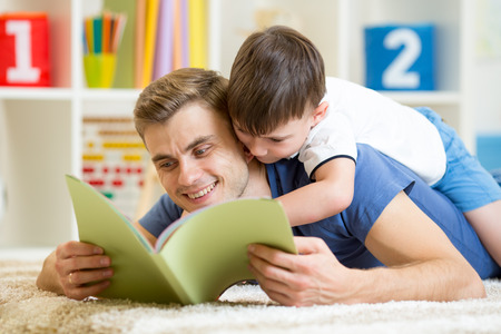 father and his son read a book on floor at home