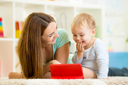 mother and kid play at tablet computer photo