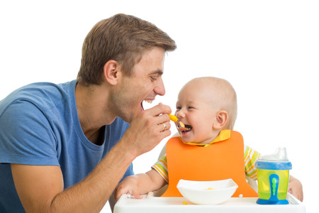 father feeding baby son photo