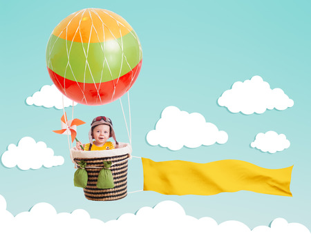 cheerful kid on hot air balloon with banner in the sky photo