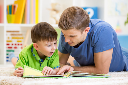 two parents: kid boy and his father read a book on floor at home Stock Photo