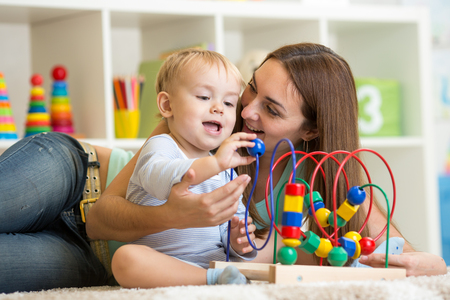 kid and mother play with educational toy indoor photo