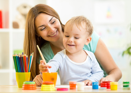 cute mother teach her son kid to paint