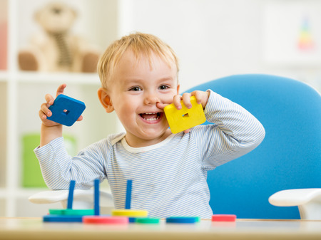 little baby boy playing with building blocks photo