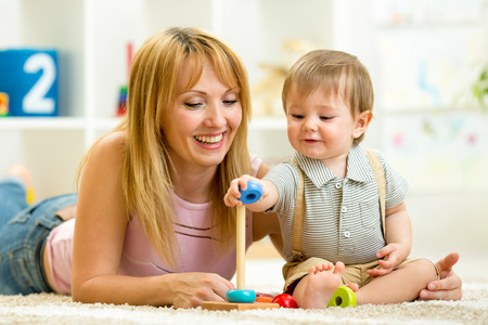 cute mother and kid boy playing together indoor photo