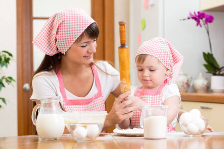 Mother and kid preparing cookies together at kitchen photo