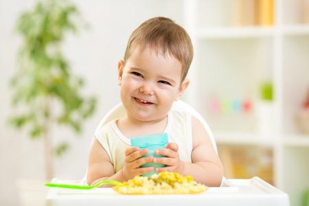 glimlachend kind jongen eten en drinken binnen