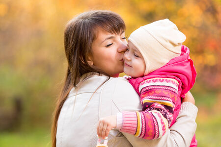 Happy woman and kid in golden autumn background. Mom kissing daughter. Mothers day holiday concept photo