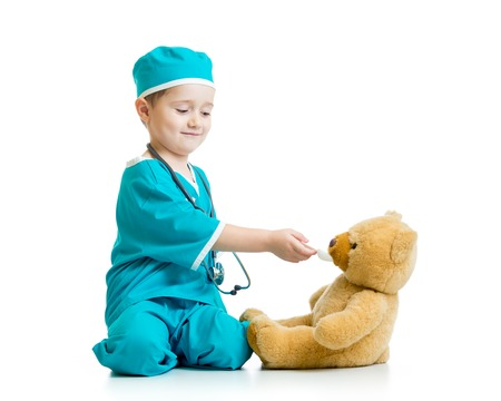 boy kid playing doctor with plush toy photo