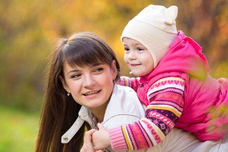 mother with kid girl outdoor in fall photo