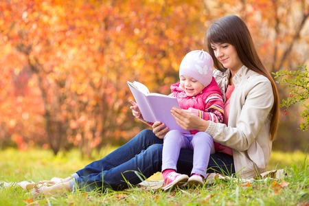 mother and kid reading a book outdoors in autumn photo