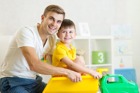 toy truck: kid boy and his dad playing with toy trunk Stock Photo