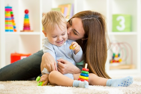 mother helping baby: happy mother and child son play  indoor at home Stock Photo