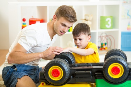 child boy and father repair toy car photo