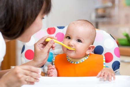baby food: smiling baby girl eating food with mom on kitchen