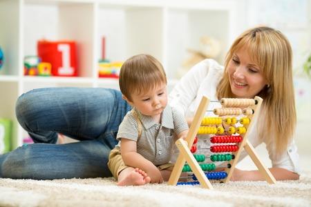 abaco: niño y la madre jugando con ábaco en casa Foto de archivo