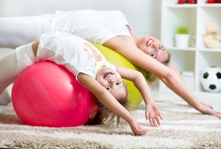 kid girl and mother doing gymnastic together indoors photo