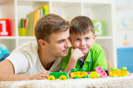 man with his kid son playing together at home photo