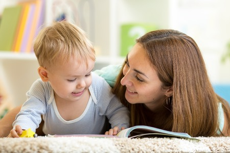 mother reading a book to kid boy at home Stock Photo