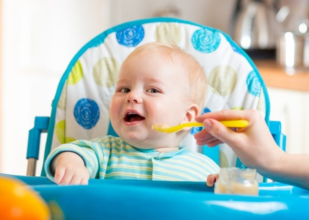 baby boy eating food on kitchen at home photo