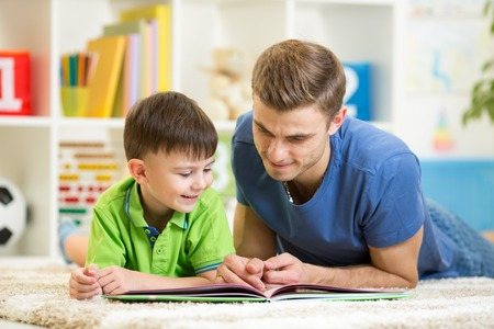joy of reading: child boy and his dad read a book on floor at home Stock Photo
