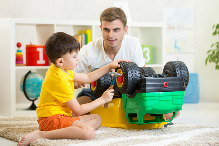 toy truck: child boy and his dad repair toy car Stock Photo