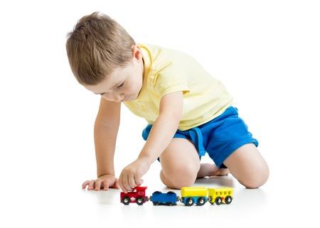 kind jongen spelen met speelgoed op wit wordt geïsoleerd