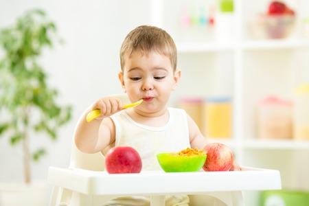 funny kid boy eating healthy food indoors Stock Photo