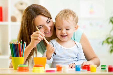 painting drawings: mom and kid boy painting together at home