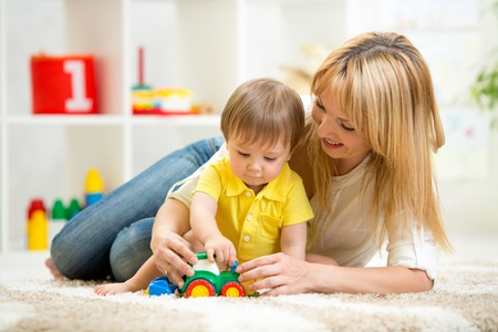 2 people at home: child boy and woman play with toy indoor