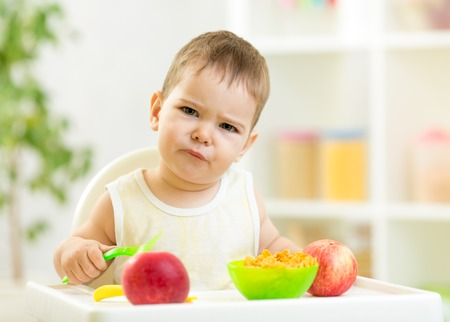 displeased kid with healthy food at kitchen