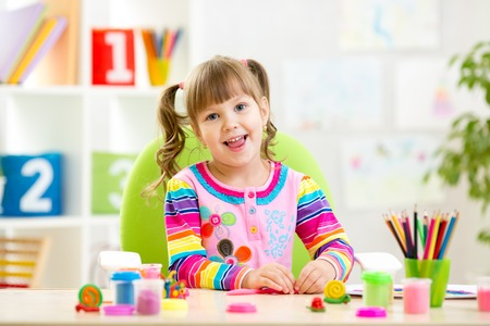 Little child girl playing with colorful clay photo