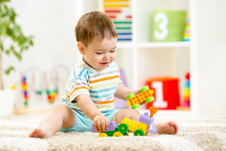 inside the house: kid boy playing with building blocks at home or kindergarten