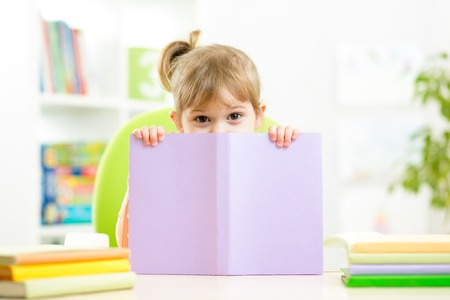 Cute child girl hiding behind book indoors photo