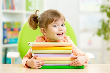 Smart kid girl preschooler with books in primary school